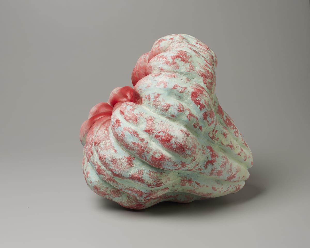 Akoda (Pumpkin), Katsumata Chieko, 16 ⅛ inches x 16 ⅛ inches x 16 ⅛ inches, stoneware with pigment. The ceramic object  is pumpkin-like, laying on its side at a ¾ turn to the left. It has bulbous, ridged sections that wrap around to the center, which is open and caving in on itself. The bulging sections seem to taper off to small nubs and become freed from each other as they curl inward towards the dark hollow at the center. There is a pale, minty green underlayer of pigment with bright red pigment applied here and there to the bumpy ridges that gradually increases until all around the opening is completely red.