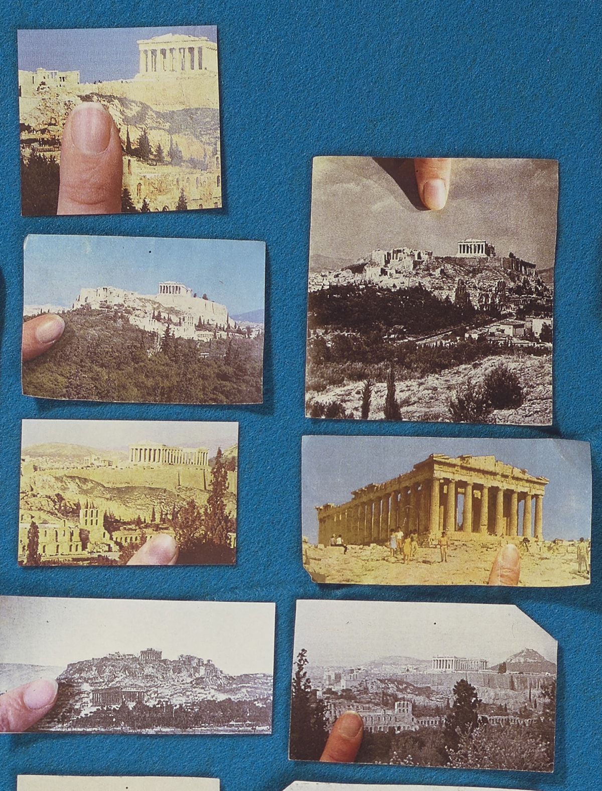 Detail: View of the artwork showing two vertical rows of images. The first row contains four pictures of the Acropolis, the first three in color and the last in black and white. The second row has three clippings, the first and last in black and white and the third in color. Each show the Acropolis from a different viewpoint, close-up or from afar. They also contain the image of a fingertip.