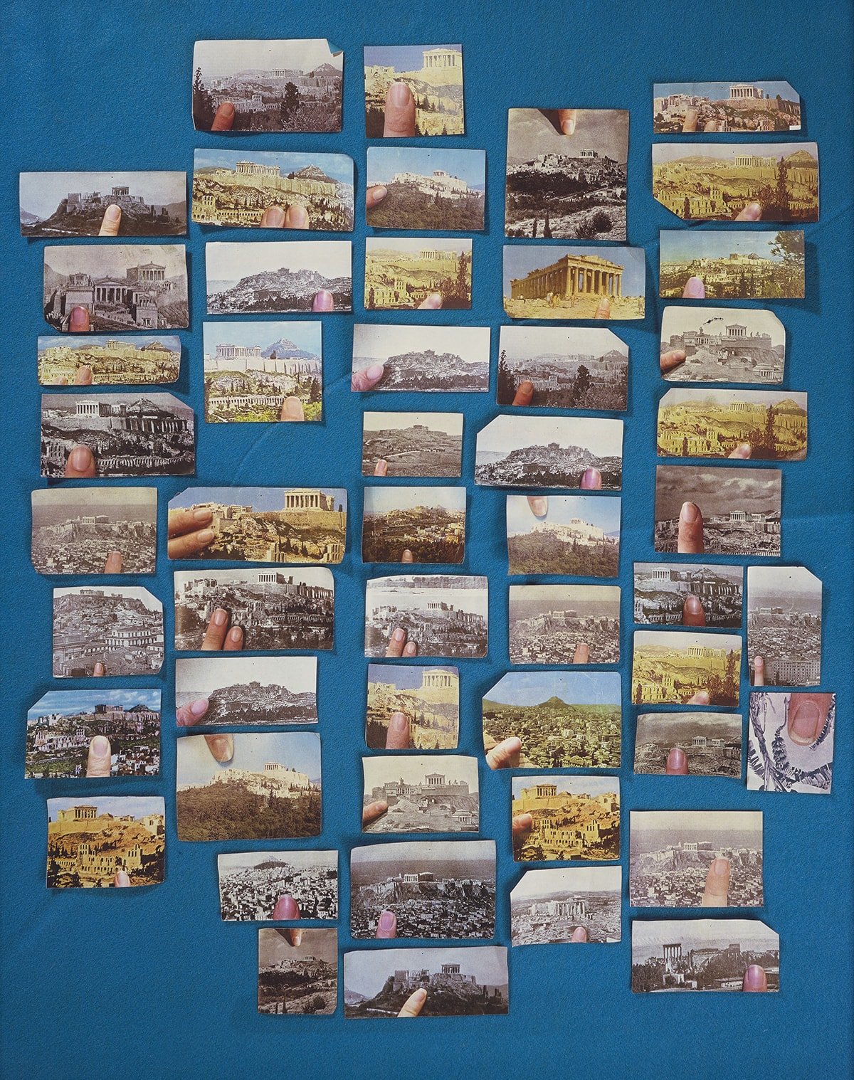 Encyclopedia Grid (Acropolis), Sara Cwynar, 40 x 32 inches, chromogenic print mounted on Plexiglass. A vertical rectangular print showing 51 postcard size images of the Acropolis arranged on a blue felt ground. The images are different sizes, both in color and black and white and mostly in a landscape format. Each also contains the image of a finger or two as if holding the picture. They are arranged in five vertical rows with the last row at right having an additional two images in portrait format. One of these images is the only one that does not show the Acropolis but instead a black and white picture of palm fronds and a banana bunch with a fingertip in color.