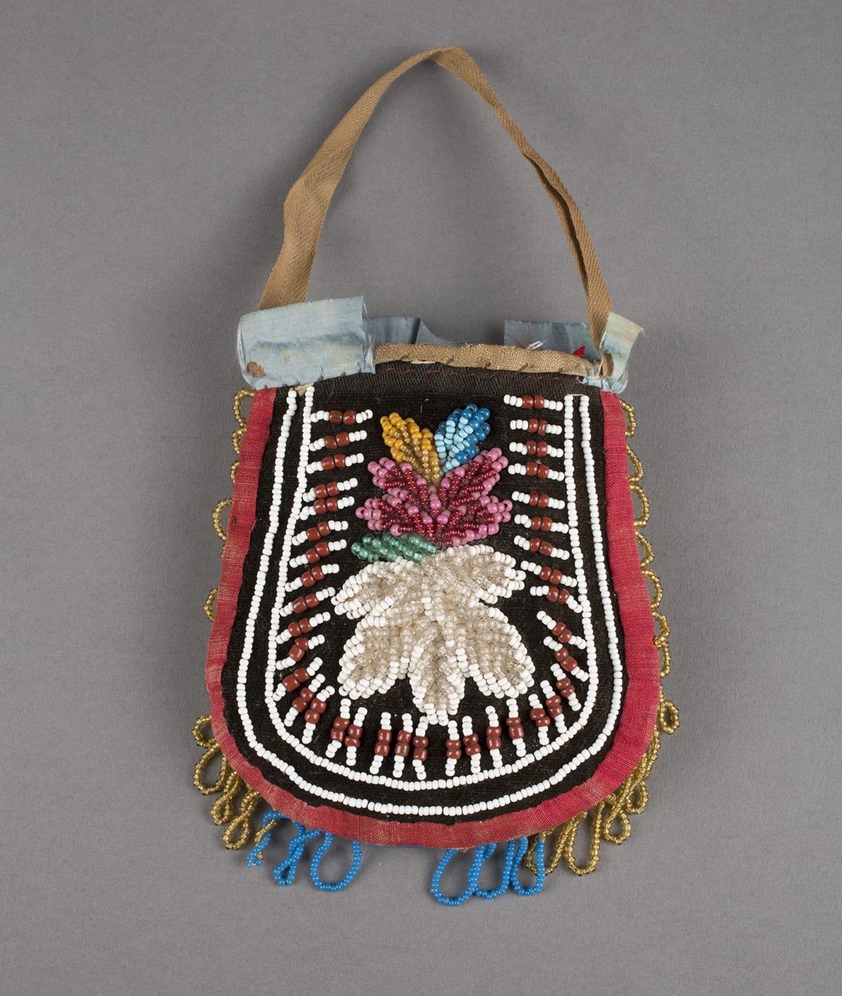 Haudenosaunee/Iroquois artist, Pouch, 8 x 4 inches, cotton, silk and glass beads. A photo of a colorful U-shaped pouch with handle against a gray background. The pouch is slightly narrower at the top then widens at the bottom. At the center, set against black velvet is a large, white, beaded flower topped by a pink, beaded flower with pale green, gold, and blue, beaded leaves. Surrounding the flowers are white and brick-red beadwork lines composed of three white beads, two larger brick-red beads, then three white beads. Each line radiates outward from the flowers at center. Two lines of white beading encompasses the center designs running along the edge of the pouch. At the outer edge of the pouch is a red cotton border with loops of gold beads along the sides and turquoise blue beaded loops along the bottom. Some areas of beading are missing at the bottom center and at the left edge. The top of the pouch shows a thin, short, tan cotton handle. Pale blue ribbon embellishes the opening of the pouch but is partially missing, exposing the hand stitching along the pouch's opening.