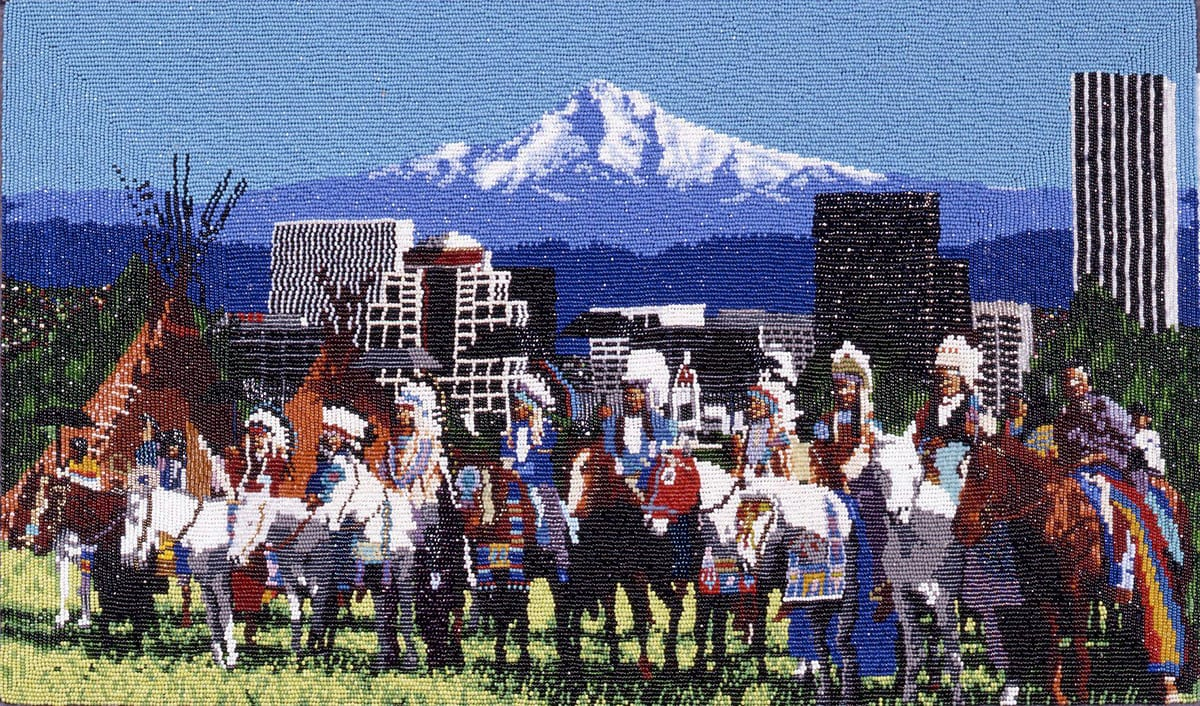 The Gathering, Marcus Amerman, 10 1/8 x 17 inches, glass beads on cotton cloth. A horizontal, rectangular work depicting a grouping of individuals on horseback arranged in a line in front of the Portland skyline with Mt. Hood in the distance. The grouping takes up the lower half of the work. They are shown on a patch of pale green grass wearing white feather headdresses and finery in blues, brick red, white and yellow. Their brown and white horses are adorned in similar colors. Just behind the group on the left are 2 brown tipis. The cityscape in the middle ground is composed of geometric buildings beaded in gray, white and black set against the blue and white mountains and blue sky in the upper half.