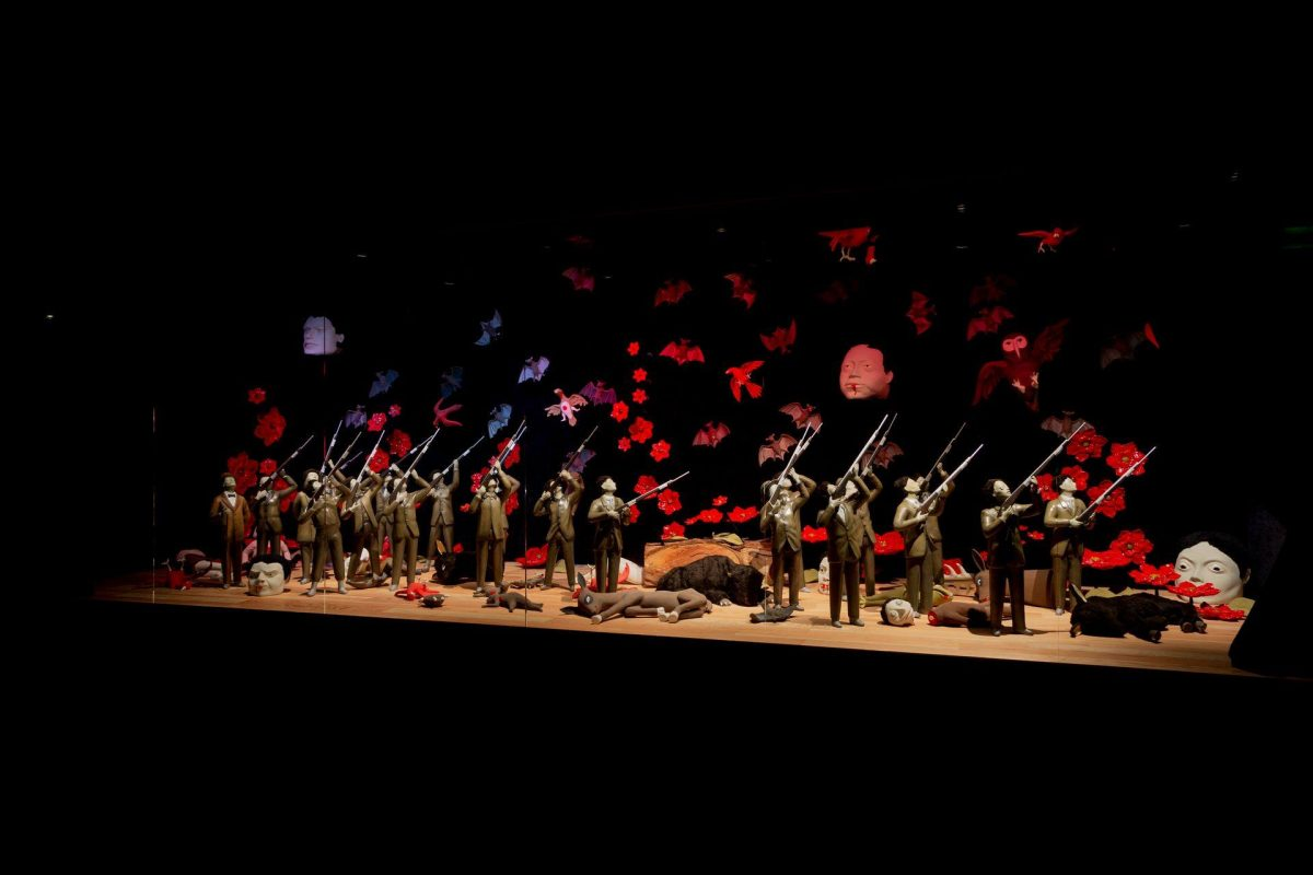 Diorama displaying an array of figures dressed in business suits pointing rifles upward towards floating red flowers, birds and bats in flight, and two disembodied heads. The ground at their feet is strewn with animal corpses and more disembodied heads. The figures are grouped most densely at the left of the diorama. There are thirteen, all clad in brown suits. Only one figure at far left can be seen without a rifle. Instead, this figure looks on holding a cane and wearing a derby and a bow tie. At center, a large log separates the two groups of shooters. At right are eight shooters, similar in look to the rest. The area above the figures is filled with red birds and gray bats and a large, brown owl. Groupings of red flowers rise from the floor of the diorama and reach upward into the sky area. Two large heads float at far left and right of center. They stare straight ahead, have light-colored skin, dark hair, and blood seeping from their mouths. The floor of the diorama is scattered with various animal bodies and parts. Donkeys, birds, squirrels, and buffalo lie among large and small human heads. The scene is surrounded by darkness.