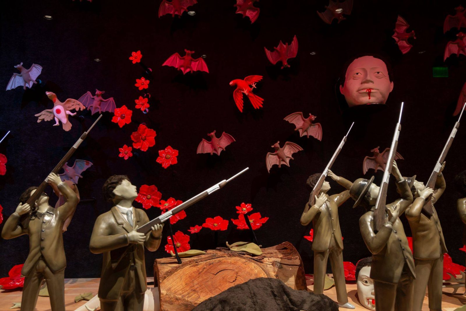 Detail: Two figures stand at left with rifles raised separated from a group of three more figures in much the same pose. The sky area above them is filled with bats and birds and red floating flowers. One bird at left has a red splotch on its chest and outstretched wings. At right a large human head floats among the birds and bats just above the figures' rifles.