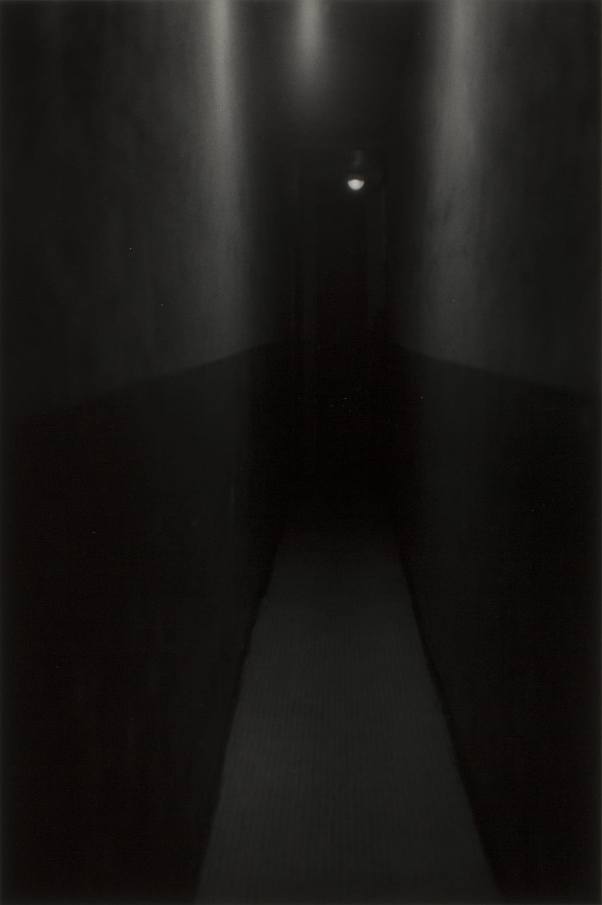 "Hallway, New York. Roy DeCarava 1953. 12 15/16"" x 8 5/8"". Gelatin silver print. Landscape oriented black and white photo. View down a long, dark, narrow hallway. The bottom half of the walls are dark black and the top half dark gray. At the distant end of the hallway is a narrow door that is closed. Above is a single white light with a dome cover."