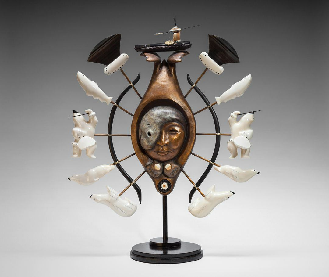 A multi-media sculpture composed of three main segments. At center is a bronze seal seen with its hind flippers at top and its head at bottom. A round opening in the center of the seal's body holds a woman's face partially covered by the profile of a silver-gray seal. Round ivory inlay circles in cream and orange are on the seal's front flippers at bottom. Another round opening at the seal's head holds woven baleen surrounding an ivory circle in cream and orange. Five brown spokes radiate out from each side of the central seal and are tied to dark, gently curving half hoops that cup the seal body. At the end of each spoke are ivory figures, each side mirroring the other. The sculptures are from bottom polar bears, seals, dancers holding drums and drumsticks, fish and ulus (knives). Facial features like eyes and noses and details on the dancers clothing are in black on the almost white ivory. The ulus have ivory handles with black dot decoration and short, dark fan shaped blades. The sculpture is topped with a hunter in a canoe set on the seal's flippers. The hunter holds a fishing spear and coiled rope and wears wide-brimmed hat rendered in orange and cream ivory. The sculpture stands on a single post set into a round base.