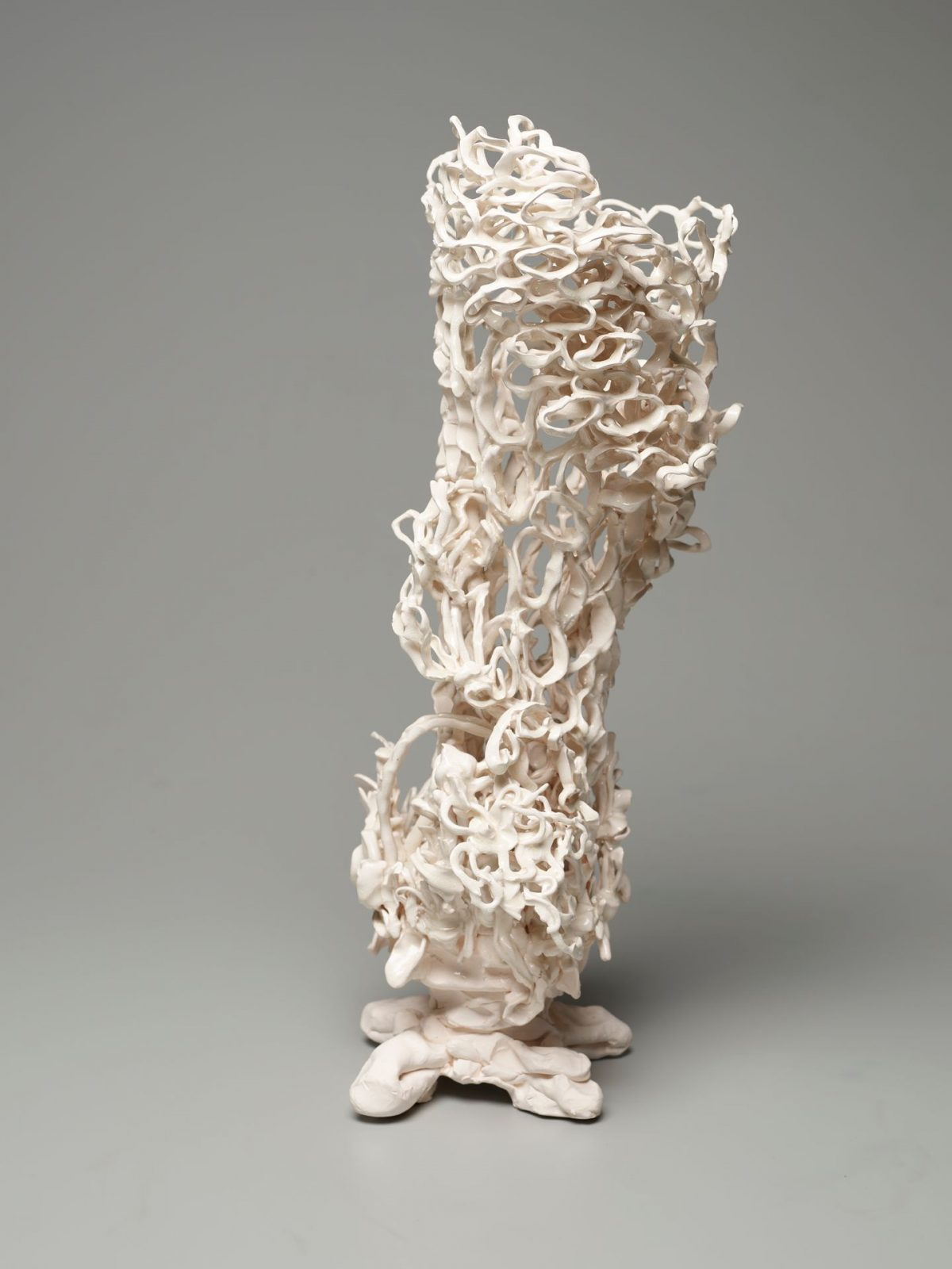 An open-work, vertical sculpture evoking the shape of a vase in creamy white. The surface is composed of oval clay loops that connect irregularly to create a highly textured lace-like body that sits on four folded clay coils. The structure appears to lean slightly to the left in this view and shows clay loops both crowded and compressed in areas like upper right and stretched and spaced in the lower left part of the sculpture. This gives the work an organic quality of perhaps coral or a sea creature.