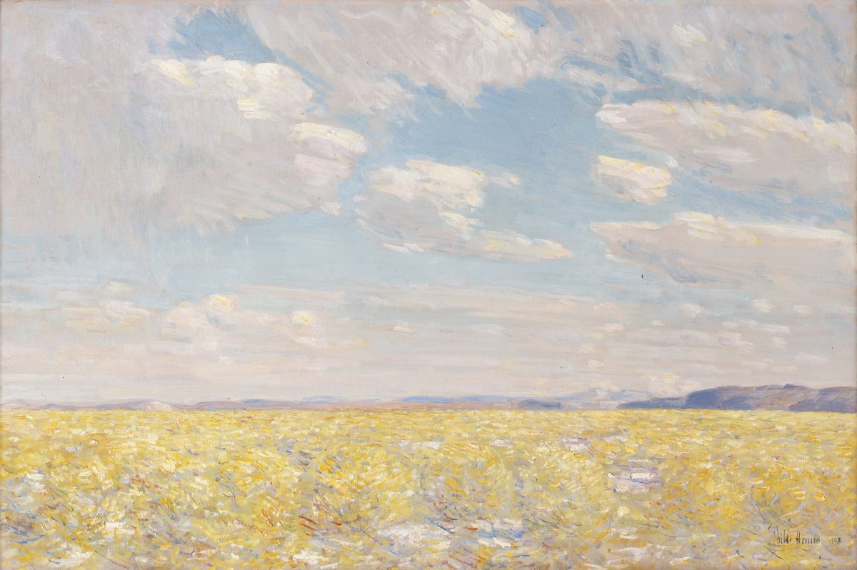 Afternoon Sky, Harney Desert. Childe Hassam. 1908. Oil on canvas. 20 ⅛ in x 30 ⅛ in. Landscape painting of the desert in Harney County, Oregon. The foreground is covered with short, sharp, yellow and white brushstrokes with orange and red highlights that make up the desert foliage resembling sage brush. Beyond the desert, near the middle of the painting, soft blue and purple lines show the distant mountains. Above them the sky fills the top two thirds of the painting. The blue sky is filled with both large banks of clouds and a few single oval-shaped clouds in the middle. The clouds appear light gray and white with soft yellow highlights along the edges. From a distance, the painting portrays a soft, warm view of the landscape. A close view reveals distinct short strokes and the blending of multiple colors.