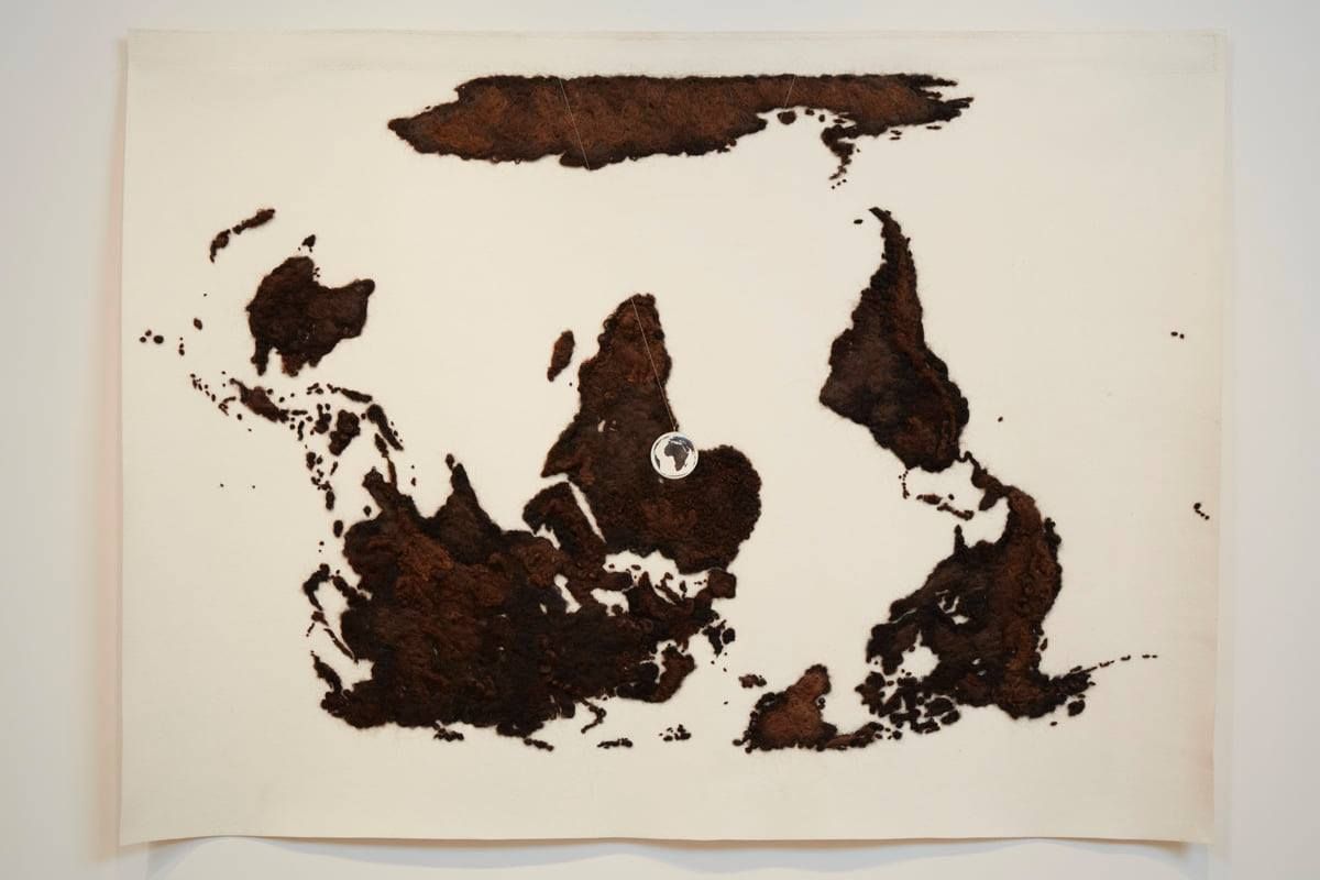 A landscape-oriented work of a flat map of the world rendered in brown human hair on a cream-colored wool felt ground. The map is upside down so Antarctica is across the top, North and South America are at right, Australia is at left and Africa is in the center. The land masses are rendered in brown hues of human hair giving them a fuzzy, textured appearance. Viewing the map upside down makes it appear to be an abstract work of scattered large and small irregular shapes. Suspended in front of the map is a small, clear acrylic ball through which the continent of Africa can be seen, right side up.