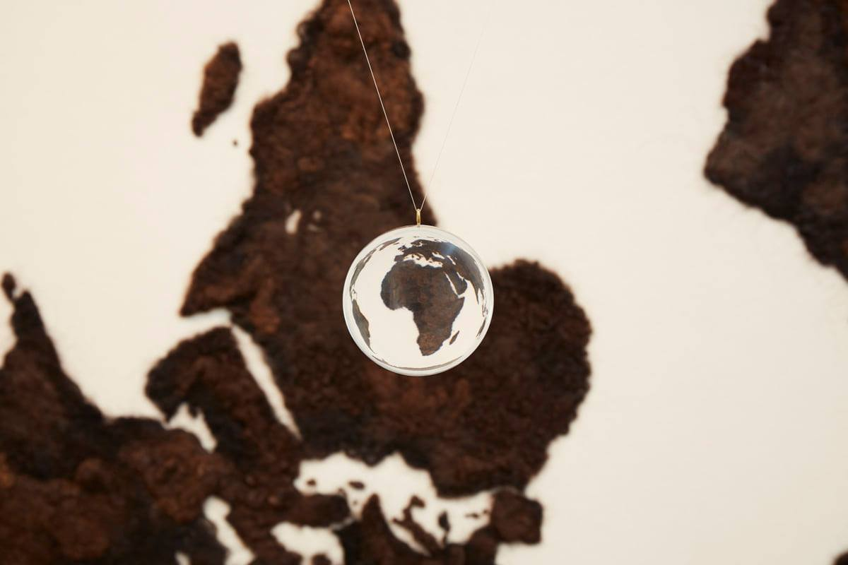Detail of acrylic ball suspended by two near-transparent lines and showing the continent of Africa, now right now up, surrounded by distorted images of the other land masses. A portion of map is seen behind it slightly out of focus with Africa at center.