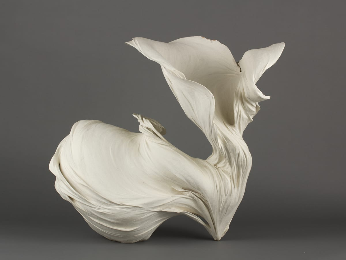 Flow #1. Fujikasa Satoko, 2011. Stoneware with matte white slip. 26 ⅛ inches high x 27 inches wide x 23 ⅛ inches deep. This sculpture resembles a light, flowing fabric garment billowing weightlessly in the wind. The sculpture touches the display surface in two points. The contact on the right is small and pointed. The material appears to flow upward and outward to the left from this point. The material flowing to the left twists and unfolds into a large round billow that has a strong sense of movement. The material moving upward from the point flows up in a thin, vertical flow that twists and opens into a funnel shape with multiple layers unfolding along the outer edges.