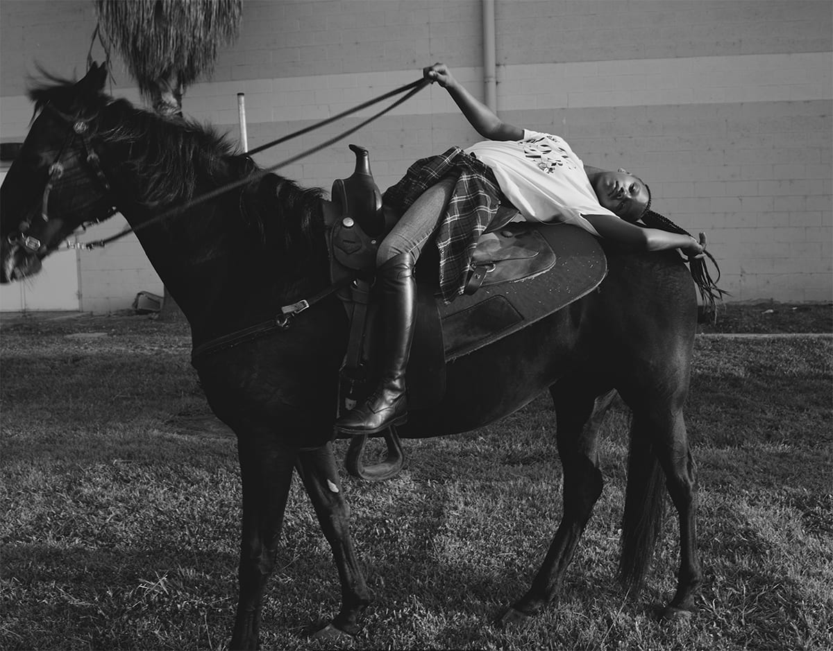 "Morganne with Ebony. Melodie McDaniel. 2017. Photograph, archival pigment print. 33"" x 44"". Black and white photograph of a young Black individual posing on a tall black horse in a field of short grass in front of a light cement brick building with a palm tree to the left. The tall, thin rider is wearing black riding boots, jeans, a light colored t-shirt with undecipherable letters on it, and a plaid shirt tied at the waist. The rider is laid back in the saddle, back arched across the back of the horse, right arm gently extended holding the reins straight, and left arm outstretched, hand resting near the horse's tail along with the rider's ponytail of long braids. The tack has a simple design of thin leather straps and small silver buckles. The horse stands, left foot forward, head raised, mane blowing in the wind, with nose and mouth partially out of frame and slightly out of focus."
