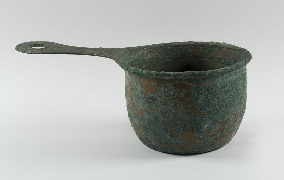 Saucepan, unknown Roman artist, 4 7/8 x 13 ¾ x 7 3/8 inches, bronze. A time worn pot with a rough, mottled, gray-green and bronze surface with a long, flat handle. The body of the flat-bottomed saucepan bows out slightly from its base and has a shallow lip that curves outward from the pot's body. It has rough, crusty, gray-green corrosion on its surface with bits of smooth brownish bronze underneath showing through. A set of three very thin parallel grooves are incised around the pan's top, just below the lip and more on the lip itself. More thin lines are seen on the interior of the saucepan. A flat handle protrudes from the left side of the pot. It narrows in the middle then widens into a rounded end with a circular cutout of its middle. More incised grooves form two circles around the cutout.