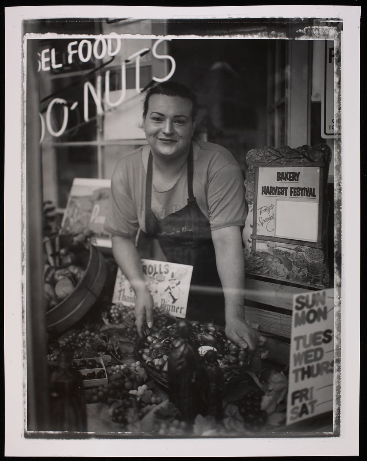 "Kat, from the series North Portland Polaroids, Bobby Abrahamson, gelatin silver print, image: 13 5/16 x 10 1/16 inches; sheet: 14 x 10 15/16 inches. A portrait oriented, black and white photograph of an individual seen through a storefront window arranging produce and smiling directly at the viewer. Their dark hair is pulled back, and they have dark arched eyebrows, a dimple on their right cheek and a beauty spot on their left above their mouth. Their smile is warm and welcoming. They wear a short-sleeved t-shirt under a dark apron. Their hands reach down in front of them to arrange a large bowl of olives amid bunches of grapes, small boxes of cherries and other kinds of produce. The figure is flanked by small store signs. One elaborately framed one to the left reads ""Bakery Harvest Festival"", to their right is an out of focus sign in the background and one is directly in front of the figure and advertises ""Rolls"" and ""Thanksgiving Dinner"". At top left a neon sign is partially seen. It reads ""…El Food"" and ""…O-Nuts"". Across the lower section of the photo, a horizontal streak of white is visible, possibly a light reflection on the store window. Behind the figure are elements of the shop: a paned glass window and doorway. A narrow uneven white line along the outer edge of the photo frames the scene."