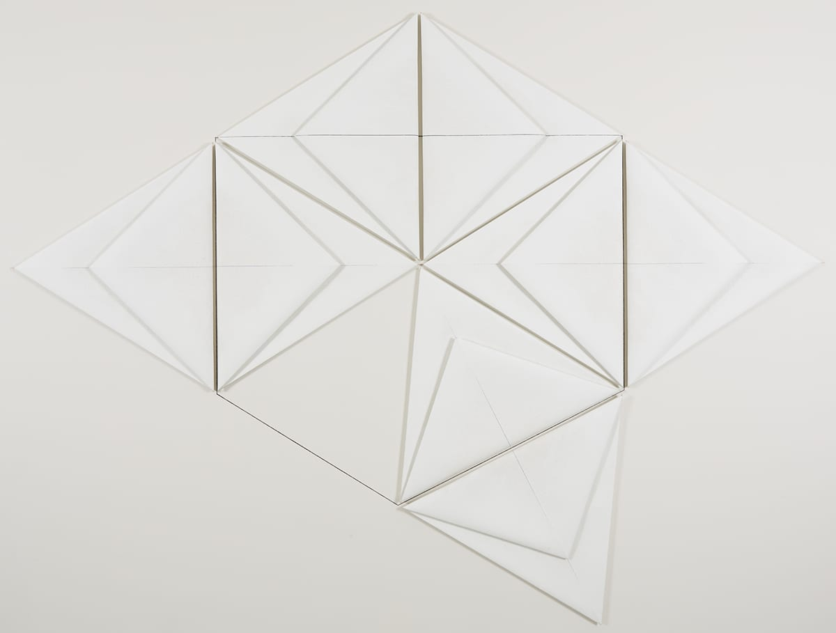 Saqqarah, from the series Egyptian Paintings, Dorothea Rockburne, 69 ½ x 93 inches, oil, gesso, and graphite on linen. A series of white-on-white triangle shapes layered and outlined to create a wide diamond shape with an extra triangle protruding from its lower right edge. The larger diamond shape contains smaller triangles that overlay other diamonds and triangles. Graphite marks the canvases and the wall behind it creating more lines, diamonds and triangles, as well as an outlined cube shape.
