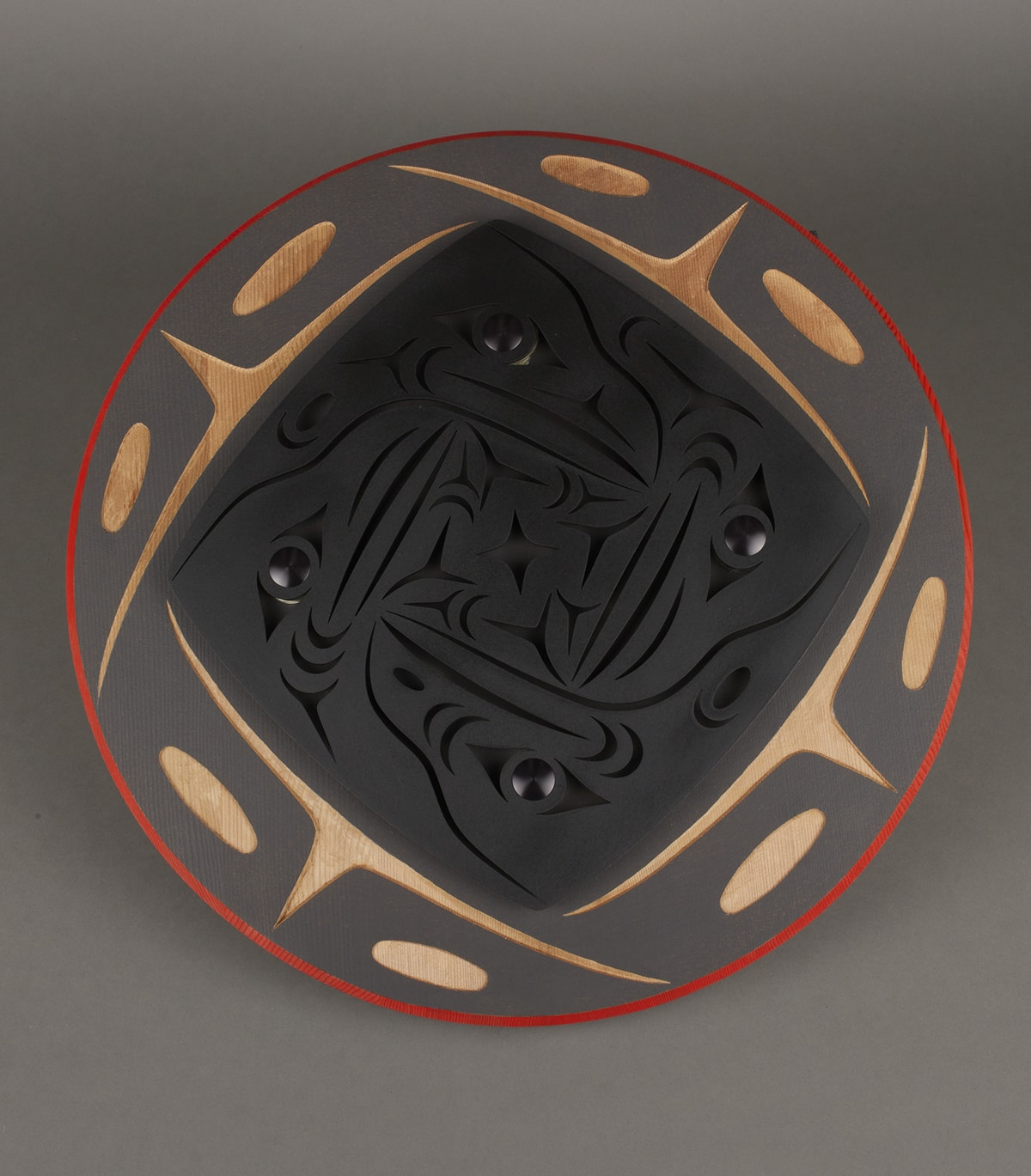 Circling Ravens II. Shaun Peterson. 2014. Pigment and Cor-Ten steel on red cedar. 2 in x 22 in diameter. Round wooden circle with a bright red edge, a strip of flat gray with carving revealing the natural cedar color. The pattern of a beak with two oval eyes as seen from a front-facing perspective is repeated four times around the circle. Inside is a flat black square with rounded edges with four crow heads carved into the black with shiny black marbles as eyes. The raven heads are viewed from a side perspective and have intricate carvings revealing eyes, beak, face feathers, and a neck. A smaller square in the middle of the ravens is filled with repeated patterns that resemble crow footprints and a four point star in the middle.