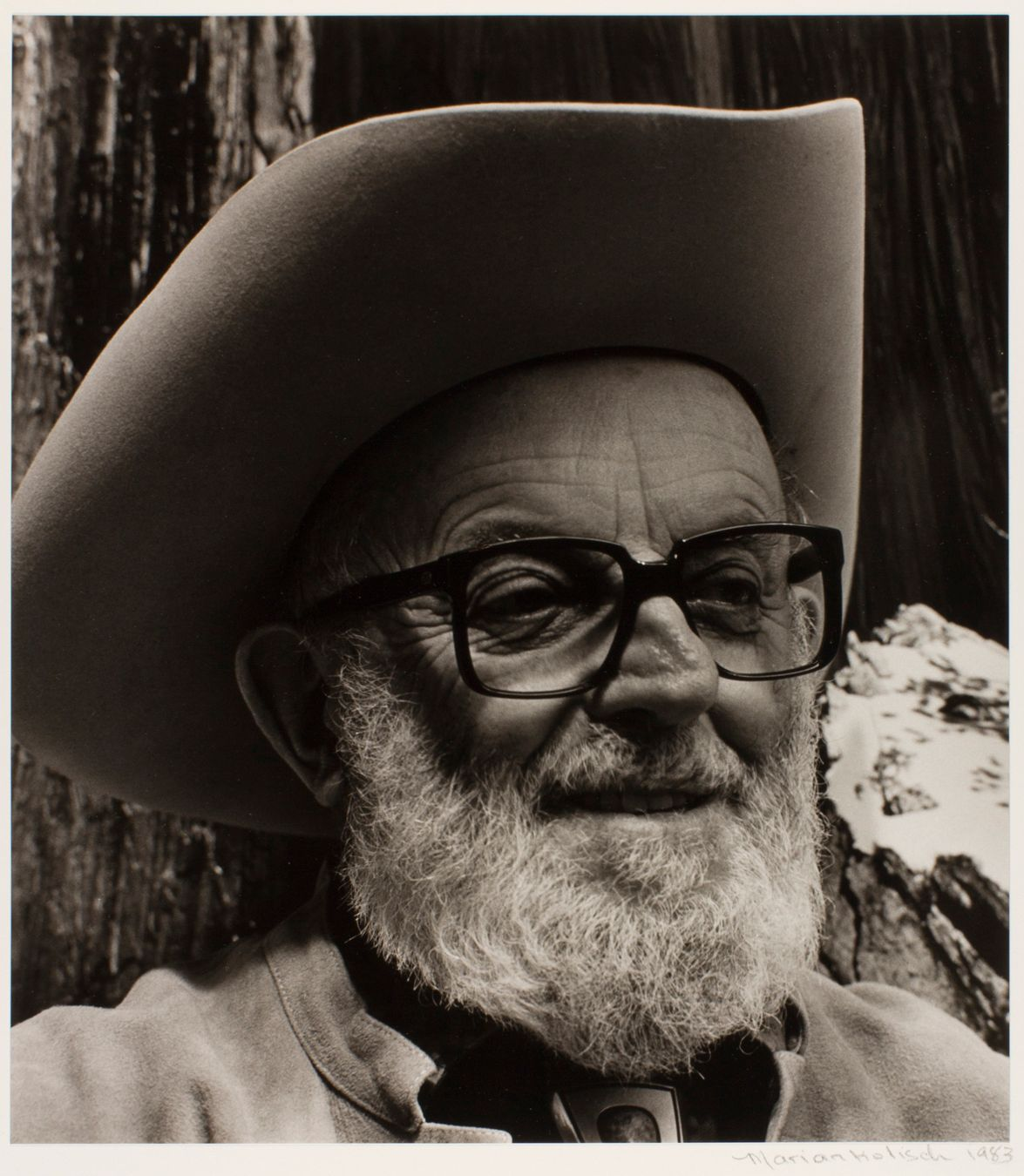 Ansel Adams, Marian Wood Kolisch, gelatin silver print, image/sheet: 11 3/8 x 10 1/16 inches. A black and white portrait of Ansel Adams, an older white man with a gray beard, wearing glasses and a broad brimmed hat. The photo shows the head and shoulders of Adams, looking slightly to the right. He wears dark, square framed glasses. His face is lined and his nose somewhat crooked. He wears a white beard and a slight smile with lips parted. A cowboy hat sits pushed back on his head creating a shadow near the crown of his head. His light-colored, collarless jacket is just visible. He is posed in front of the textured bark of a tree.