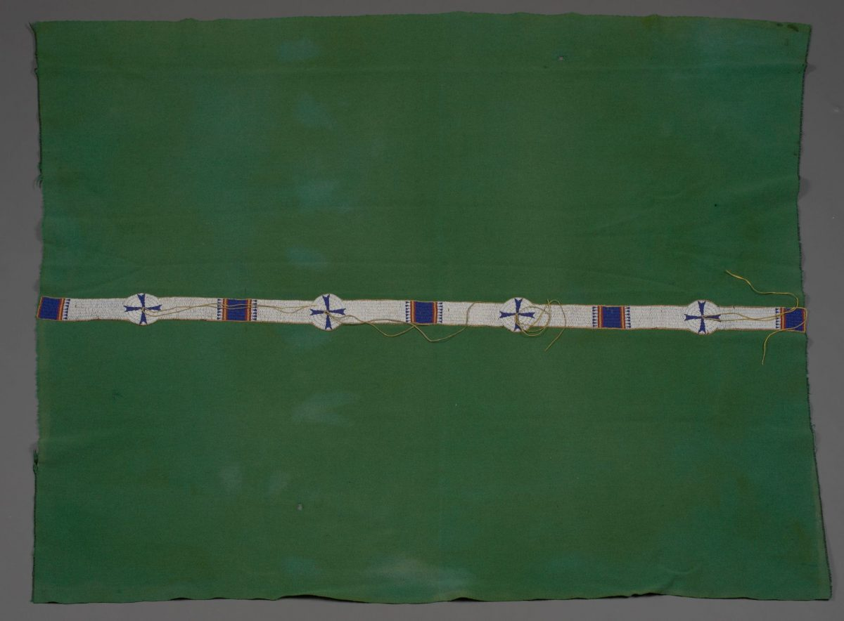 [Image description: Cheyenne artist, Blanket, 73 ¾ x 55 ½ inches, wool, glass beads. A rectangular, leaf green blanket with a narrow strip of beading running lengthwise along the middle. The blanket shows some discoloration where the fabric has faded and its edges are frayed where the stitched binding has come away. Stretching across the work, a narrow strip of white beading is punctuated by five blue beaded squares that are flanked on either side by slim yellow and red stripes and rows of blue beaded triangle shapes. Four round white beaded circles with blue crosses are interspersed between the squares. Pairs of long beige cords emanate from the circle centers, some lay stretched across the beading, some are coiled.]