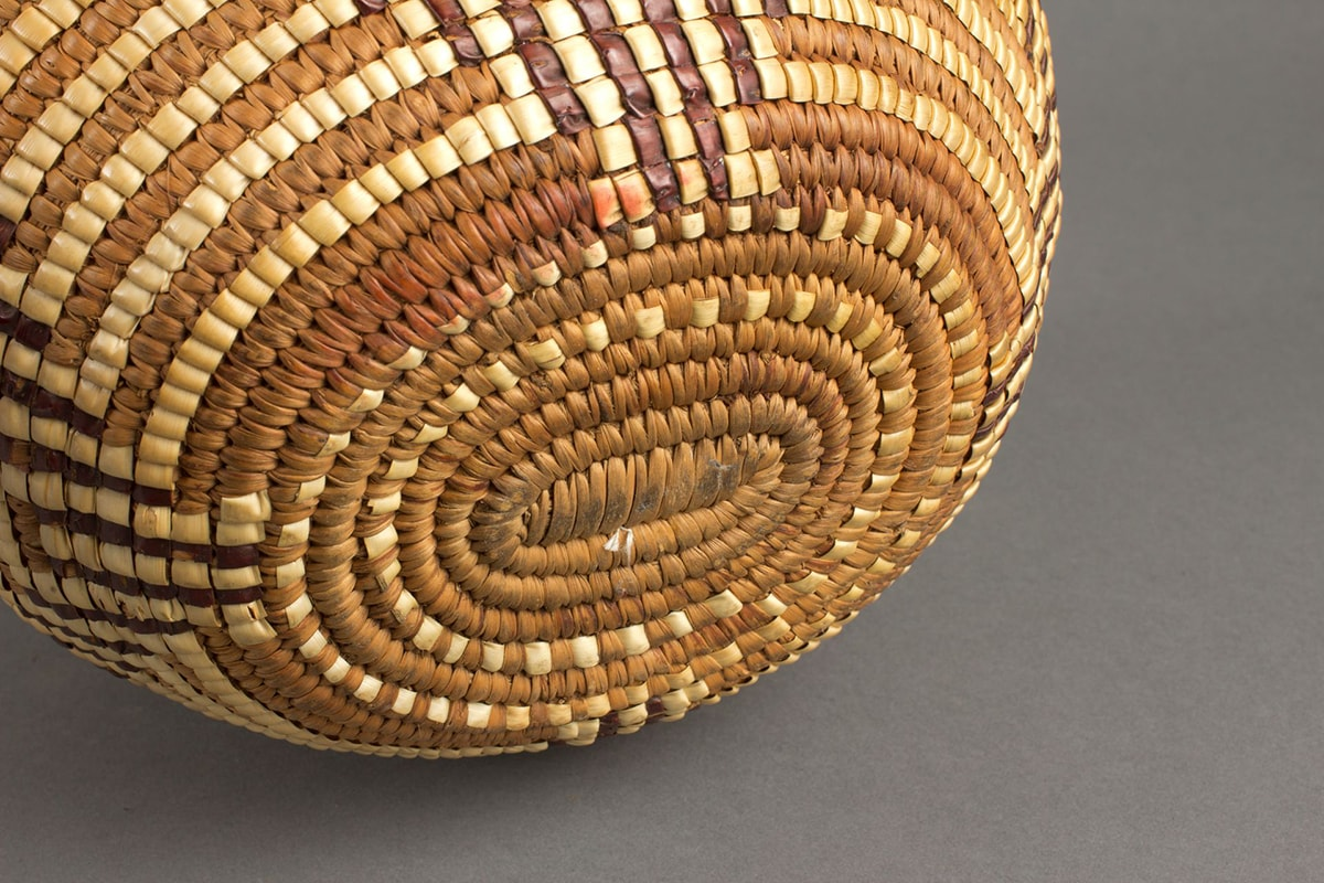 """Detail of the base of the basket. Oval shaped base in light beige and medium brown. The lighter color material creates two """"dotted"""" oval around the center. Slight wear is evident at the center and pale reddish staining is seen on its upper edge."""