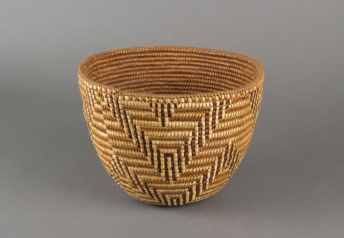 Image description: Basket, Cowlitz artist, cedar root, beargrass and dyed beargrass, 7 ¾ x 10 x 9 ¼ inches. 1. A round woven basket featuring a chevron pattern rendered in three tones of materials: light beige, medium brown, and dark brown. The basket has a wide mouth and gently narrows to a small base. It is tightly woven using the medium brown tone as a background on which the light beige and dark brown are used to create pattern. The dark brown and pale beige combine to repeat a double chevron pattern around the basket in an upper and lower row. At the center of each chevron at the top is a small, inverted triangle shape.