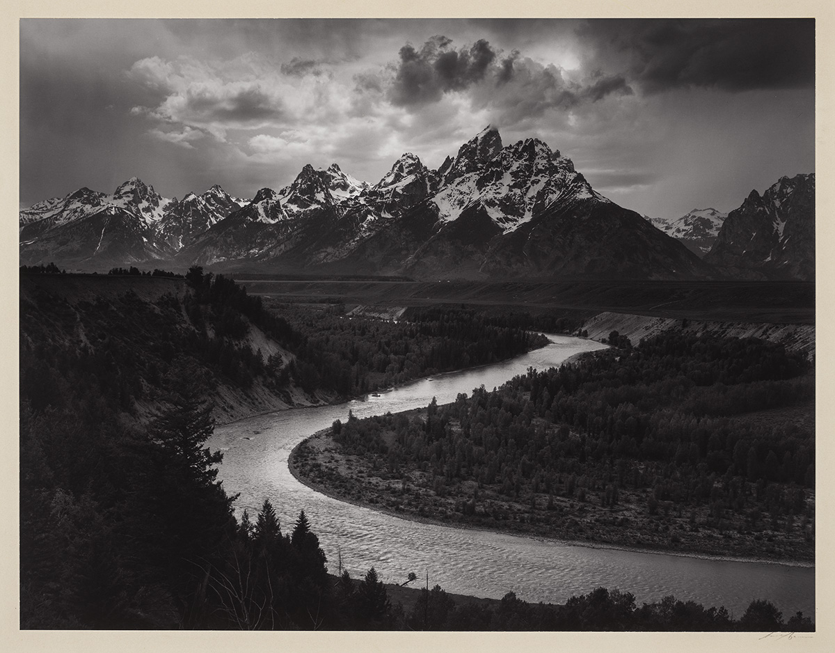 The Tetons and the Snake River, Grand Teton National Park, Wyoming, Ansel Adams, gelatin silver print. A landscape photograph showing the jagged peaks of the Grand Teton mountain range as a backdrop to the sharply curved Snake River in the foreground. The mountains begin a third of the way down from the top and stretch across the width of the photo. Snow-covered, jagged peaks overlap against a dramatic sky of clouds with sun breaking through. Below the mountains, low rolling hills meet the S curved river seen emerging from the vegetation at the center right. The river crosses diagonally to the left and switches back to the right at the bottom of the work. Steep scrub covered hills rise from the river edge at left. Low lying trees and vegetation fill in the right of the photo, while evergreen trees are seen at the bottom in the foreground.