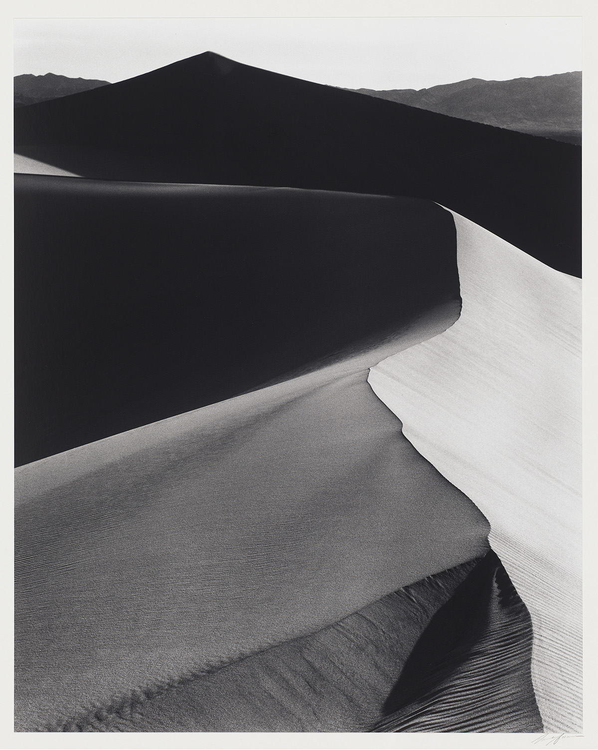 [Image description: Ansel Adams, Sand Dunes, Death Valley National Monument, California, gelatin silver print. A black and white, portrait-oriented photograph of steep sand dunes shown in high contrast shadow and light. The ridge of the main dune begins at upper left, crosses to the upper right then zig zags down to the lower edge of the photo. The steep sides contrast in tone. The right side of the dune is bathed in light and appears as pale gray, while the left slope of the dune is split between being almost black at its upper portion then changing to a medium gray as the dune catches more sunshine. In the background a black, horizontal dune appears, stretching from left to right contrasting with the highlights of the main dunes' ridge. At upper right in the background, a distant dune appears as a medium gray tone.]