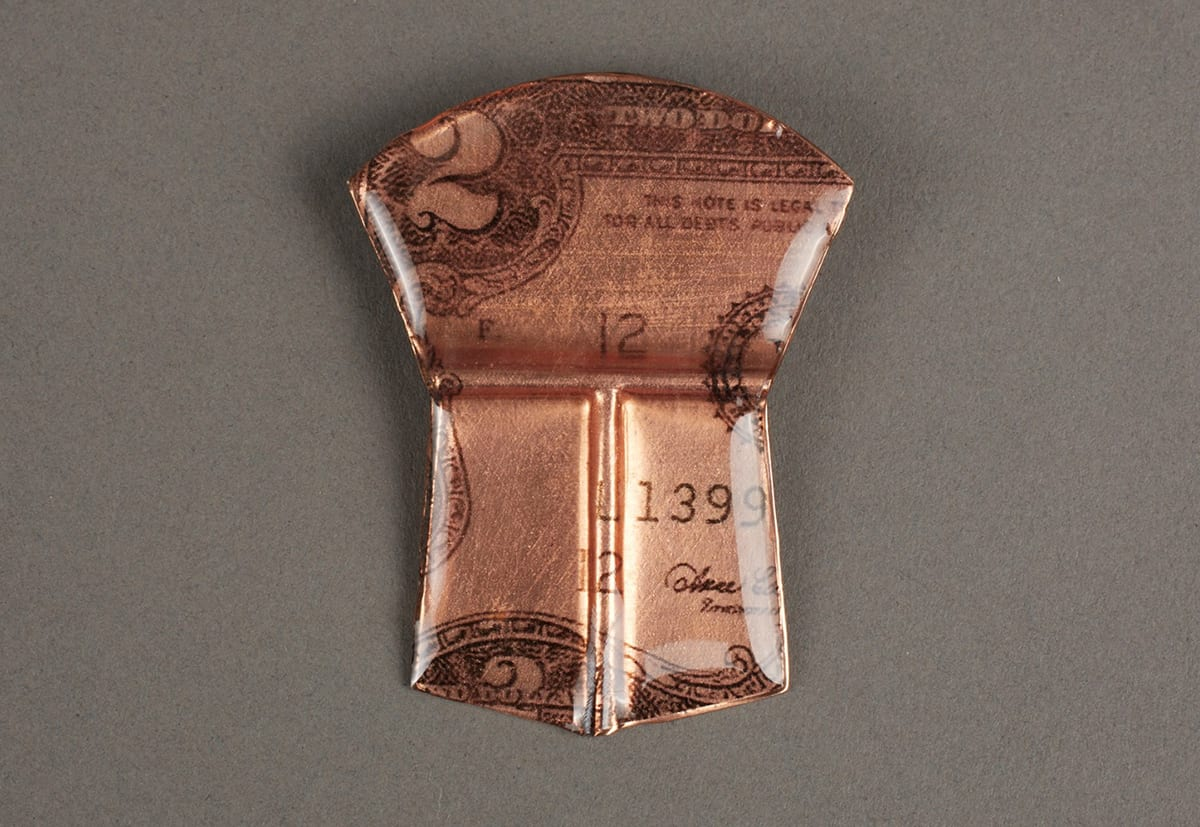 """Image description: Two Dollars, Alison Bremner, resin and paper on copper, 2 x 1 ½ inches. A small shield-shaped object with a copper hue and details of a two dollar bill. The object is divided in two main parts: the upper and lower portions. The upper portion is shaped like a fan with a curved top that narrows at the sides and is divided from the lower part with a horizontal indentation in the glossy resin that covers the object. The fan contains the top left corner of a two dollar bill. A prominent number two is seen at left along with the elaborate scrollwork in the bill's border. The words: """"This Note Is Legal T…For All Debts Public"""" is seen at right. A capital letter """"F."""" and the number """"12"""" are also seen on the plain lighter copper colored background along with part of a circular seal. Below the upper fan shape the shield is further divided in two with a vertical indentation. These two trapezoid shapes come to point at the center and show more of the bill including the numbers """"1399"""" at right, a number """"12"""" at center and a portion of the treasurer's signature at lower right. The finish is glossy and smooth with beveled edges. the numbers """"1399"""" at right, a number """"12"""" at center and a portion of the treasurer's signature at lower right. The finish is glossy and smooth with beveled edges."""