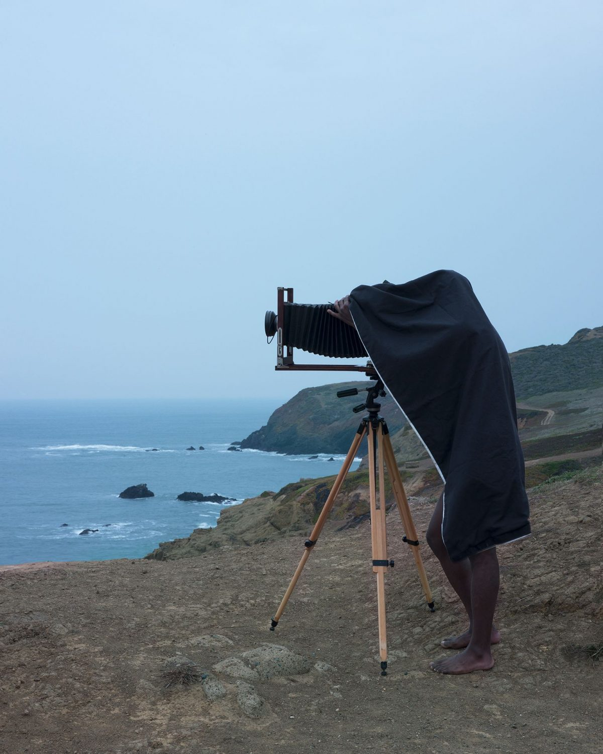 Image description: Double Vision (Record), Jonathan Calm, pigment print. A vertical rectangular photograph of man using a camera on a tripod near an oceanside cliff. The man is seen from the side, his camera pointed to the left. The camera has a large black bellows attached to a lens and stands on light-colored wooden tripod legs. The man is mostly concealed under a dark cloth with only his bare legs and the fingers of one hand visible. He is dark skinned and barefoot. He stands on rough, brown ground with cliffs and the ocean behind him. The upper half of the photo contains a pale blue sky.