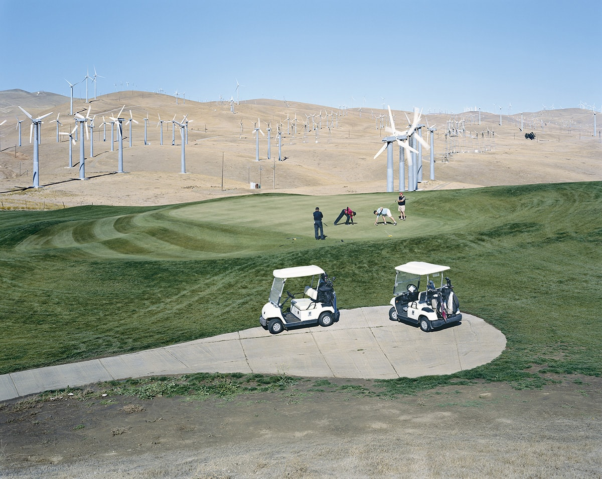 Image description: Altamont Pass Wind Farm, Mitch Epstein, photograph, chromogenic print. A landscape photograph of a golf course set amid bare, brown rolling hills with wind turbines. The top half of the photo features a cloudless pale blue sky and low brown hills dotted with silver wind turbines. Some are fairly close and some recede into the distance. A green, manicured golf course cuts across the middle of the photo. Four figures stand on the green, two appearing to bend down to tee up and the two others standing on either side of them. Striped lawn mowing marks are evident on the left side of the green. Below, a paved path has two small white golf carts parked one behind the other. At the lower edge of the photo, the grass tapers off to a dusty sandy flat area that fills the bottom fifth of the photo.