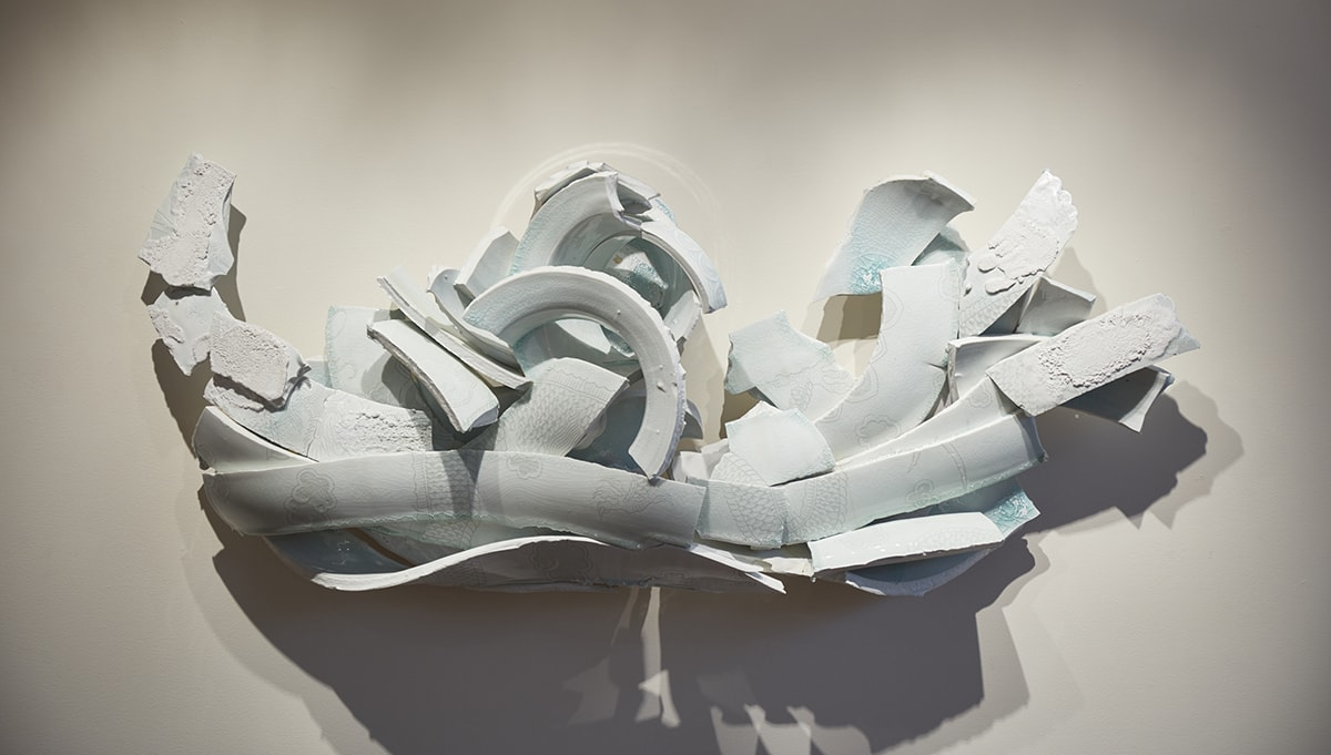 Image description: Jar with Dragon and Clouds, Steven Young Lee, porcelain, white slip, glaze, epoxy, steel, 40 x 58 x 10 inches. A large, wall-mounted installation of broken porcelain shards. The shards are a pale blue green in color and are arranged overlapping, some with their decorated surfaces facing outward, some showing the interior of the jar. The pieces float on the wall without visible means of support in a gentle crescent shape with each end raising slightly. At center, the two parts of the round rim are placed one atop the other. Large portions of broken coils undulate outward. Some are placed flat; others standing on their edges. At a distance, the shards appear to be a solid blue green but are delicately decorated in deeper hues of blue green showing details of dragon scales and the crazing of the surfaces. Some shards of the vessel have rough, bubbled surface that contrast with the smoother exterior views of the shards. The work is lit from above causing shadows to be cast below it.