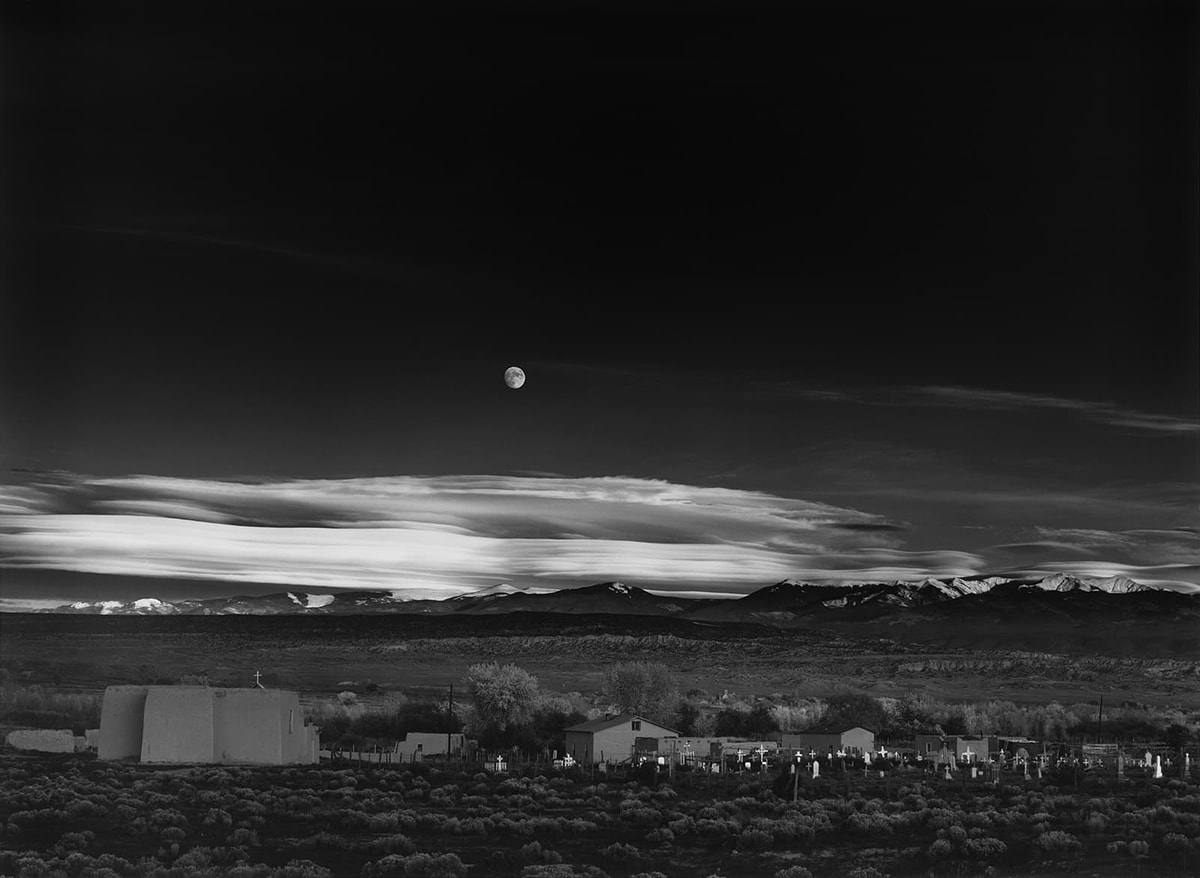 Image description: Moonrise, Hernandez, New Mexico, Ansel Adams, 1941, (negative) printed later, gelatin silver print. A black and white, landscape photograph showing a moon in a dark night sky over mountains, a church and graveyard. The photo is divided roughly in half with the top portion holding the dark, almost black sky. Towards the center of the work the sky lightens, and wispy clouds stretch across the photo. An almost full moon sits just left of center in the lighter sky above the light gray clouds. A snow-peaked mountain range sits under the clouds with scrubland below it. At far left a pueblo-style church with steep flat walls rises in the foreground topped with a small white cross. Low lying outbuildings and trees continue across to the right side of the photo where they meet with a cluster of crosses and headstones. Each cross is slightly different, and all seem to reflect the light and show up brightly against the darker background. Dark scrubby bushes continue to the bottom of the photograph.
