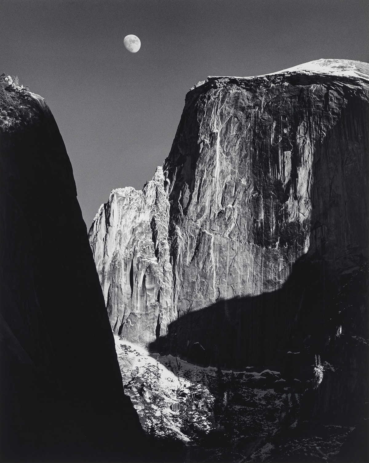 Image Description: Moon and Half Dome, Yosemite National Park. Ansel Adams. 1960. Gelatin silver print. Black and white photo of the sheer cliff wall of Half Dome in Yosemite under a waxing gibbous moon. The white moonlight reflects off the expansive Half Dome cliff edge highlighting the detailed texture in the rock appearing as vertical white lines. The jagged edges of the cliff are sharp and the top of the dome on the right appears smooth. A black edge of another cliff appears on the left side in the foreground. A large shadow in the shape of a backward L covers the right side of Half Dome extending from the right side of the photo into the middle. The rocks at the bottom of the two cliffs are slightly blurred and partially covered by shadows.