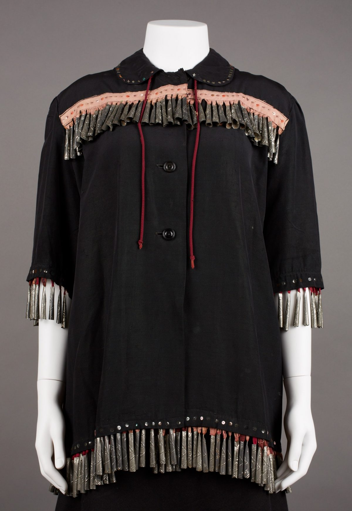 Ojibwa artist, Blouse, 30 x 39 inches, cotton, plastic buttons, tin, and sequins. A black, hip length shirt with elbow length sleeves and a small, rounded collar. Patterned metal jingles set closely together hang from a short yoke edged with a faded peach strip of fabric, stitched and embellished with sequins. The round collar is edged with star shaped sequins and has two long strings that hang to mid garment. Two large black buttons fasten the shirt at mid chest. The sleeves and hem are also edged in evenly spaced sequins. More jingles drop from under the sleeve and garment hem suspended by cloth loops, their colors now ranging from red to faded peach. The shirt's hem dips slightly at the sides approximately reaching the wearer's finger tips.