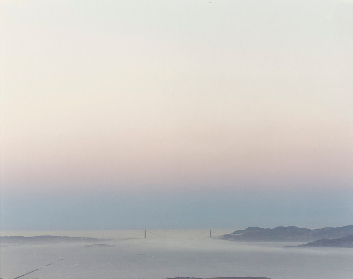 Image Description: Golden Gate Bridge 8.4.98 6:16am Richard Misrach. 1998. Photograph, chromogenic dye coupler print. Landscape photo showing the Golden Gate Bridge in the distance under the pastel colors of the sunrise. The bottom fourth of the photo shows peaceful bay waters covered with a light layer of fog. Dark peninsulas extend from either side of the bay just before the barely visible two pillars of the bridge. Calm water extends past the bridge and fades into the light blue sky. A thin layer of light purple extends beyond the blue followed by a light cream and blue sky.