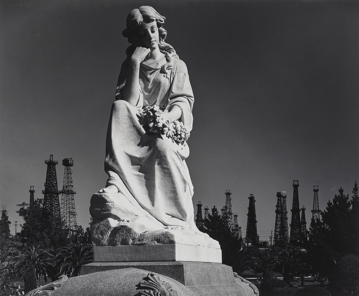 Image Description: Cemetery Statue and Oil Derricks, Long Beach, California. Ansel Adams. 1939. Photograph, gelatin silver print. Square black and white photo of a statue of a female with flowing wavy hair parted in the middle and gently falling onto her shoulders. Her eyes are closed and she has a peaceful, but solemn expression on her face. The figure is wearing a flowing robe-like garment with several ripples and folds. Her chin is gently resting on the folded fingers of her right hand and her elbow is resting on her knee. Her right foot and toes peek out from under the robe. She holds a wreath of daisy-like flowers in her left hand as it rests on her lowered left knee. The sculpture is on a cement pedestal that is partially visible with rounded corners decorated with filigrees. The figure seems illuminated while the evergreen trees, fifteen oil derricks, and sky in the background are much darker.
