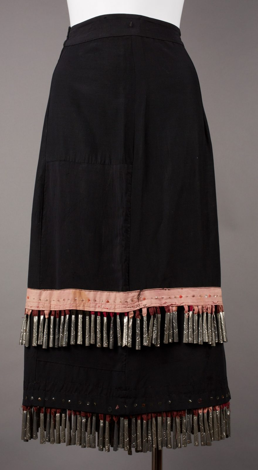 Ojibwa artist, Skirt, 27 x 31 ½ inches, cotton, plastic buttons, tin, and sequins. A long, black, slightly A- line shaped skirt decorated with two rows of metal jingles and a pale, peach stitched, fabric strip. The skirt has a flat waistband, fastens on the right side and falls in a slight flare to the hem. At lower calf level a faded peach colored strip of fabric bisects the skirt. It is embellished with a row of sequins in the middle and bordered by a line of black stitching at top and two lines of red stitching below. Jingles hang from under this strip from fabric loops in shades of red, brick, peach and black. The black skirt continues to the hem and finishes with another row of sequins on black with jingles on fabric loops extending from under the hem. The main body of the skirt is pieced in places, especially at the lower right where several rectangles of black fabric are stitched together to make up the garment. A center seam runs vertically down the skirt.