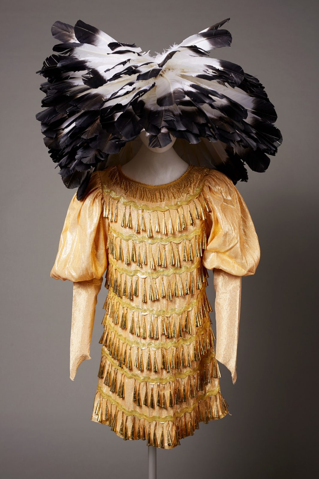 Wendy Red Star's Stands Towards the Sun, 2011. A metallic gold dress with puff sleeves on a mannequin with a large black-tipped white feathered cap obscuring the head. The dress is covered in 7 even, horizontal rows of gold jingles. The puff sleeves are drawn in at the elbows and extend into sleeves.