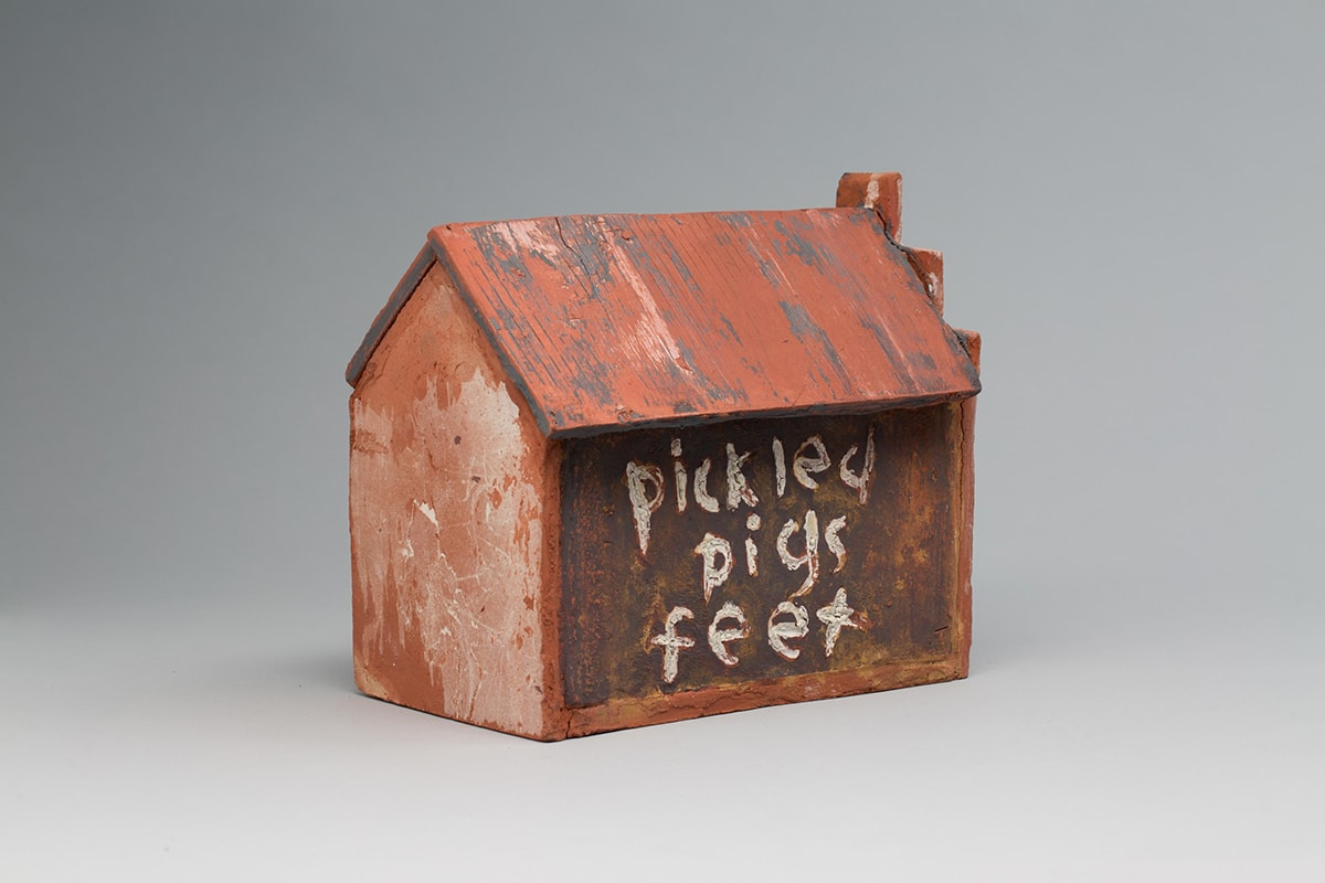 """Image descriptions: Little's Grocery (Shack #4), Willie Little, glazed ceramic, 9 ¾ x 7 ¾ x 10 ¾. 1. A three quarter view of a ceramic house with pentagon shaped ends, long sides and a sloped roof. The terracotta-colored roof has vertical ridges with deep gray and light beige portions creating a worn look. The broad side of the house is a dark brown with lighter shades of terracotta showing through. The words """"pickled pigs feet"""" is painted on one broad side and """"penny candy"""" on the other. The lettering is done in a lowercase, free hand style in a crackled, uneven, near white glaze with bits of terracotta showing through. The end of the house at right has a stairstep pattern rising from the gable, ending in a square shape at the peak. The short end of the house features lighter and darker terracotta colors that create texture and pattern."""