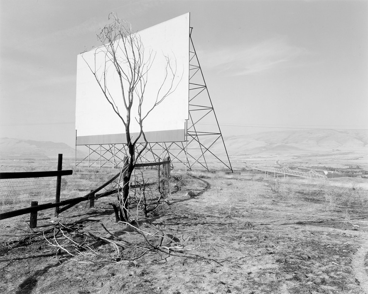 Image description: The Dalles, Oregon, Dan Powell, 1989, gelatin silver print, image: 12 11/16 x 15 7/8 inches; sheet: 16 x 19 7/8 inches. A black and white photograph featuring a drive-in movie screen and a bare tree amid an austere hilly, landscape. The movie screen occupies the upper left quadrant of the photo and shows the screen in a three-quarter view. A triangular structure supports the screen and its crossbar construction creates further triangular shapes. A small leafless tree stands near the screen and its darker branches cover most of the surface of the white screen. A dark wooden post and wire screen fence starts at center left and juts into the space behind the tree. The surrounding ground is strewn with bare branches and scrub grass. In the distance at right center and even with the bottom of the movie screen, the Dalles Bridge crosses a portion of the Columbia River. Low-slung, far-off hills bisect the photo in half. The top half of the photo shows a pale sky with light, wispy clouds.