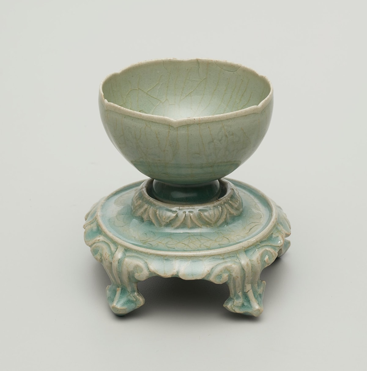 Image description: Foliated Cup and Stand with Floral Décor Korea, Jeollanam-do province, Gangjin kilns, Sadang-ri, light gray stoneware with incised and molded decoration under blue-green celadon glaze, 4 x 4 inches in diameter. A small round cup with a gently fluted rim and footed base sits on a round, decorated stand with five short legs. The cup and stand are a grayish-green with a crazed surface. The crazing creates a light brown, crackled pattern over the decorated surfaces of the work. The cup with its lip-rim mimicking a shallow flower petal edge, has molded floral pattern. The much narrower foot of the cup appears as a deeper green color and sits snugly in the raised stand. The stand's upper tier is decorated with stylized V shapes before smoothly widening horizontally. A raised rim separates the upper tier from the five decorated legs of the stand. The legs end in a blunted point with two seeming to be too short to rest directly on the display surface.
