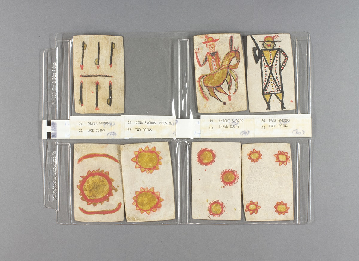"""Image description: Playing Cards, Apache artist, colored ink on paper, 35 cards, each 3 ½ x 2 ¼ inches. Seven handmade playing cards decorated in bright reds and yellows displayed and labeled on a clear plastic holder. The top row of cards shows """"Seven Swords"""" with three vertical swords over another three bisected by a horizontal sword. Next, a space is left for a missing card, """"King Swords"""". """"Knight Swords"""" is next and shows a figure wearing a hat and yellow and red uniform riding a brown horse. """"Page Swords"""" is last in the row; The figure wears a plumed hat, and its body is depicted as a long rectangle with a black X across it. Red and black dots decorate the body with smaller triangles making up the figure's legs. The bottom row of cards starts with """"Ace Coins"""" shown at a large yellow circle in center ringed with red and edged in small yellow triangles outlined in red. Two red semi circles bracket the yellow coin on top and bottom. The next card is """"Two Coin"""", two stacked yellow coins, rimmed with triangles and outlined in red. """"Three Coins"""" shows the same style of coins positioned at 11, 3 and 6 o'clock. The last card in the bottom row is """"Four Coins"""" and it uses the same yellow and red coin show one in each corner of the card. The cards rest on a clear plastic holder and paper labels separate the top and bottom rows."""