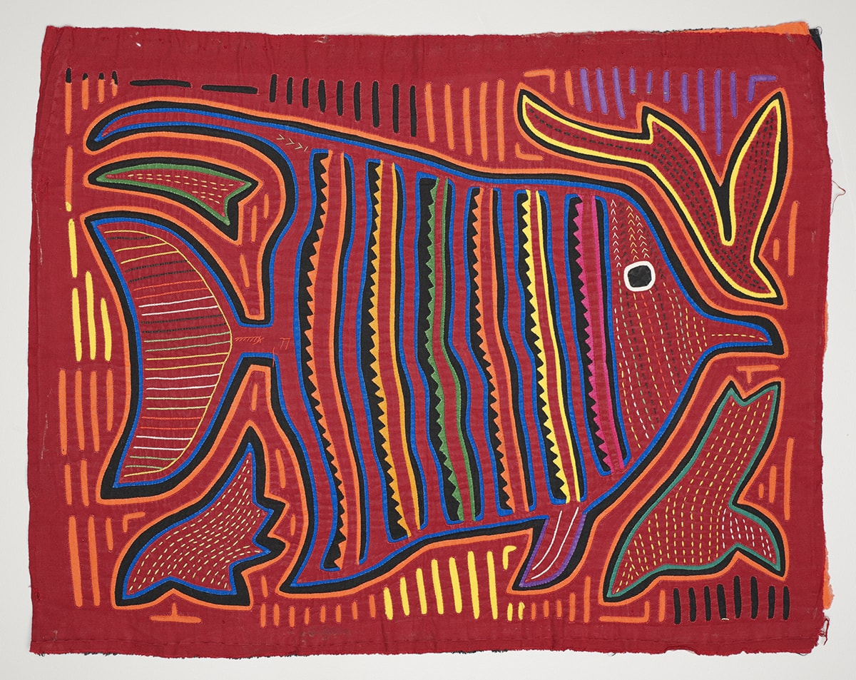 Image Description: Fish Mola. Kuna artist. Cotton. 13 ¾ in x 17 ½ in. Bright red fabric with a fish embroidered on it. The fish is outlined in a thick black line with a bright blue line against it on the inside and a bright orange line on the outside. The fish is triangular shaped and facing the right. It has a large flat tail and small fins in front. Its mouth is small and beak shaped. It has a large black eye with a white outline. Its face is a series of lines of small dots that are yellow and red. Behind the eye, solid colorful lines: blue, black, pink, red, pink, scalloped black, blue, red, blue, black, yellow, red, yellow, scalloped black, blue, red, blue, black, orange, red, orange, scalloped black, blue, red, blue, black, green, red, green, scalloped black, blue, red, blue, black, yellow, red, yellow, scalloped black, blue, red, blue, black, orange, red, orange, scalloped black, blue. The tail has several horizontal lines of varying colors (green, yellow, white, red, orange). There are also lines of various colors between the outline of the fish and the edge of the fabric (black, yellow, orange, and purple). There are four shapes at the corners of the fish. The top left is a triangular shape with a green and black outline and yellow dots. The top right is a shape that resembles a bird with a long tail diving downward. It is outlined in yellow and black and has dark spots. The bottom right also resembles a bird diving and is outlined in green and black with yellow spots inside. The bottom left is flame shaped with blue and black outlines and yellow dots inside.