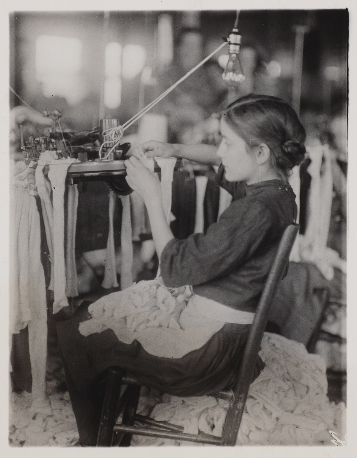 Image description: Lewis Hine, Making Stockings, gelatin silver print, 4 1/2 x 31/2 in. Vertical rectangular black-and-white photo of a young girl in profile sitting on a wood chair slightly tilted back that faces left, her hands and quiet concentration focused on a factory machine with stockings draped from it. She wears a dark dress, light apron, her hair appears to be in a low bun, and her lap is full of stockings which spill over to the floor and create a heap to her right. The background is out of focus and suggests disorderly conditions.