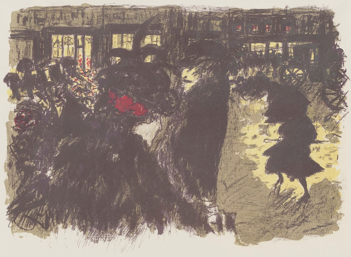 Image description: Pierre Bonnard, The Square at Evening, 1899, Color lithograph on cream paper, 16 x 20 ⅞ in. A large group of people walk through the square alongside stage coaches in front of large buildings with bright light shining from the windows. Heavy, layered strokes make up the images with details that are difficult to differentiate. A light-skinned woman wearing a black cape, large black hat with feathers protruding from the top, and red bows in her hair faces away from the viewer and takes up a two-thirds of the bottom of the lithograph. To the right a tall, thin, light-skinned man with a mustache and black coat and hat walks towards the left side of the lithograph. Behind him a shorter, thin woman with light skin looks downward and carefully steps forward while wearing a long black dress and a black hat. Yellow light reflects in the puddles around her. Behind her to the right two stage coaches drive off the paper. A large group of figures that cannot be distinguished mill about in front of the lighted windows of the large buildings. Four windows on the second floor are illuminated with reddish orange lights.