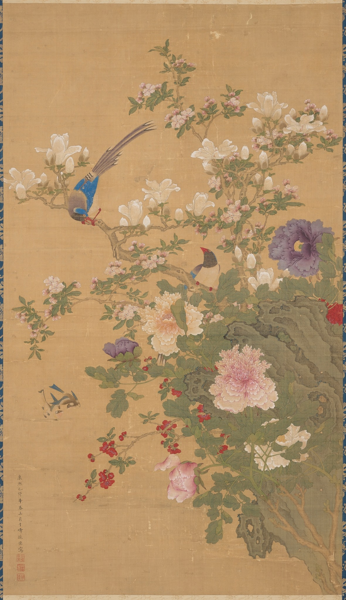 Image description: Birds and Flowers, Sun Yi, hanging scroll; ink and color on silk, painting: 48 1/2 x 27 3/4 inches; mounting; 92 1/2 x 34 inches. Detail of scroll depicting two birds perched on flowering branches. A brown bark covered branch bisects the work from upper left slanting down the lower right. A male bird grips the branch at left, grey plumed tail held high while it bows its blue capped head at its mate at lower right. Its wings are bright blue, body gray and beak, legs and feet a brilliant red. They perch among creamy white magnolia blossoms and buds, tiny pale pink crabapple blossoms and leafy greenery. A large peach magnolia blossom with its many layered, ruffled petals is at lower bottom next to a violet peony bud. The scene is set against a khaki background.