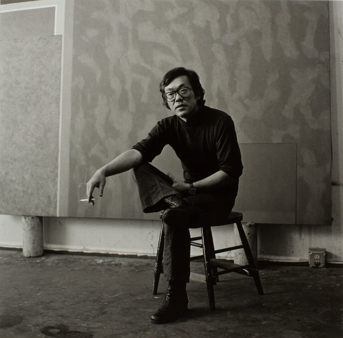 Mary Randlett, Portrait of Frank Okada, 1972. Gelatin silver print, 10 3/8 x 10 9/16 in, black-and-white square portrait of the artist, a Japanese-American male perched on stool, right foot crossed onto his left knee, in front of a large painting. He wears clothes indicative of the time: dark flared pants, leather boots, large glasses, a dark collared shirt with sleeves rolled up, and holds a lit cigarette in his right hand. He gazes into the middle distance to the left of the viewer.